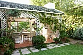 Potted climbing plants in front of roofed terrace with inviting seating area