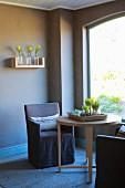 Braun getönte Zimmerecke mit Sessel um rundem Holztisch vor Fenster