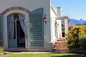 Mediterranean country house with arched door and open shutters painted grey-green