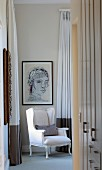 White, Rococo armchair in corner below portrait on wall