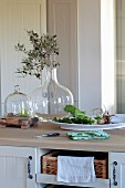 Olive branch in glass vase next to bowl of fresh vegetables on kitchen counter