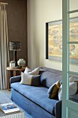 Open door with view of blue couch next to table lamp on side table in corner