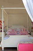 Four-poster bed with white frame and pink and white patterned pillows