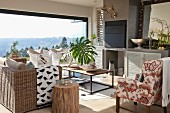 Wicker sofa and floral armchair around coffee table in living room flooded with sunlight through open, folding terrace doors