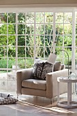 Modern armchair with pale upholstery, table lamp on side table and floor-to-ceiling lattice windows with view of garden