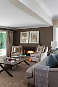 Pale armchairs with scatter cushions and sofa around coffee table on sisal carpet; open fire in brown-painted wall of living room