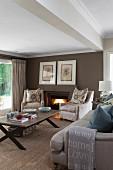 Helle Polstersessel mit Kissen und Sofa um Couchtisch auf Sisalboden, im Hintergrund braun getönte Wohnzimmerwand mit Kaminfeuer