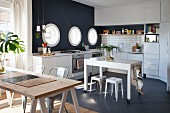 Table on castors in white fitted kitchen with black mosaic floor, black accent wall, porthole windows and wooden table on trestles in foreground