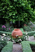 Urn at intersection of gravel paths and flowerbeds edged with low hedges