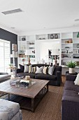 Black sofa set around wooden coffee table in living room with white fitted shelving in background