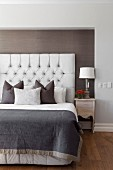 Elegant bed with scatter cushions arranged against button-tufted headboard in niche with dark brown fabric wallpaper