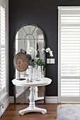 Orchids on white, round side table in front of arched, full-length mirror against dark wall