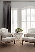 Rococo-style white armchairs and tray table in front of French windows with closed interior shutters