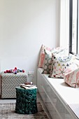 Scatter cushions with various patterns on custom window seat and stool used as side table
