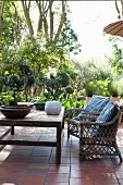 Rattan chairs and bonsai tree on wooden table on terracotta terrace with garden in background