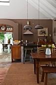 Rustikaler Essplatz mit altem Holztisch in offener Küche