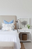 Double bed with white bedspread, arranged scatter cushions and white-painted bedside table