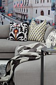 Patterned scatter cushions on pale grey sofa in front of New York mural wallpaper