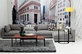 Set of coffee tables and grey sofa in front of New York mural wallpaper