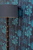Standard lamp with wooden base against wallpaper in shades of blue with pattern of coconut palms