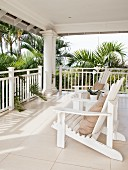 Two Adirondack chairs on Hamptons-style veranda surrounded by palm trees