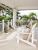 Veranda im Hamptons-Style mit zwei Adirondack Chairs umgeben von Palmen