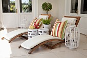 Two wooden sun loungers with brightly striped cushions on veranda decorated with lanterns and coral