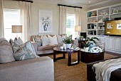 Cream sofas and two dark, wooden, round coffee tables in elegant living room