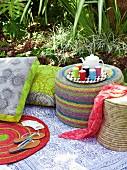 Sitzpouf, Flechthocker und floralen Sitzkissen auf Picknickdecke im Garten