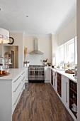 Offene Küche mit Mittelblock gegenüber Küchenzeile am Fenster
