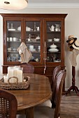 Dining area with antique chairs around wooden table in front of crockery in glass-fronted cabinet