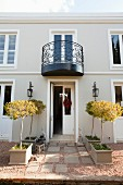 Small trees in rows of planters outside elegant house with open front door; black, wrought iron balcony on first floor
