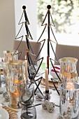 Brennende Kerze und Weihnachtsdekoration, stilisierter Tannenbaum aus Metall, zwischen Silber Windlichtern