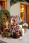 Table on terrace festively decorated with flower arrangements in wire baskets and lit candles