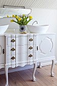 Vintage chest of drawers converted into washstand with twin countertop basins; vase of yellow tulips