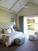 Double bed with button-tufted headboard, arranged scatter cushions and blanket; open terrace doors with a view to one side