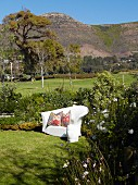 White, outdoor sofa with ethnic scatter cushions in sunny garden in front of mountain landscape