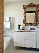 Modern washstand with white base unit below mirror with ornate wooden frame