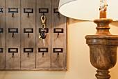 Detail of lit lamp and key rack; California; USA