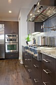 Kitchen with brown cabinets and vent hood; Irvine; California; USA