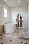 View of bathtub and bathrobes on stand in bathroom; Irvine; California; USA