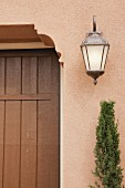 Detail of closed brown door with wall lantern at Irvine; California; USA
