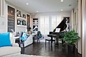 Wohnzimmer mit Arbeitsbereich, gegenüber Klavierflügel an Fenster