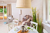 White dining table and chairs below rattan lampshade in front of pale grey sofa set in corner of wood-panelled interior