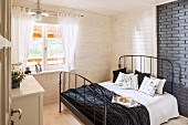 Double bed with black metal frame against grey-painted brick wall partially panelled in wood