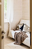 Blick durch offene Tür auf Sofa mit Tagesdecke, in Zimmerecke vor hell lasierter Holzwand