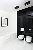 Toilet and bidet mounted on black glass wall and large, white floor tiles in designer bathroom