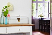 Vintage bread box and vases of flowers on console table with white drawers; view through open door into dining room with table below window