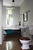 Toilet on glossy floor and vintage bathtub below window in background in bathroom painted pale grey