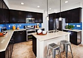 Modern kitchen with dark wooden cabinets; San Marcos; California; USA